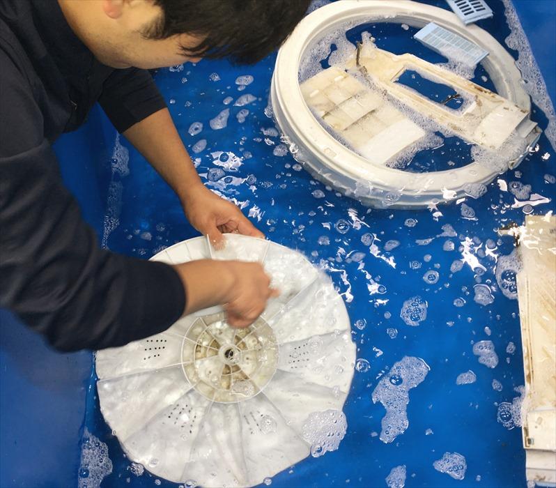 分解した洗濯槽を洗浄するスタッフ.3