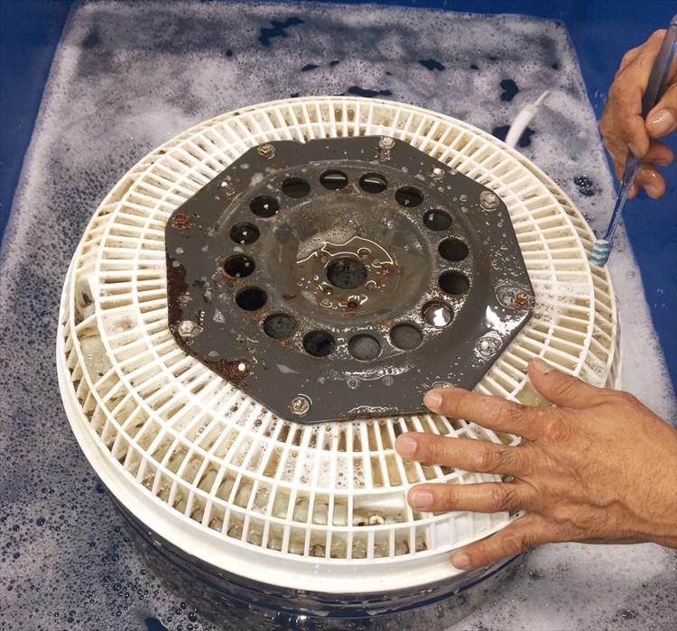 分解した洗濯槽を洗浄するスタッフ.1