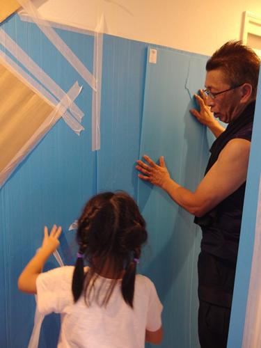 新築の養生作業を娘さんに丁寧に教えてあげるスタッフ