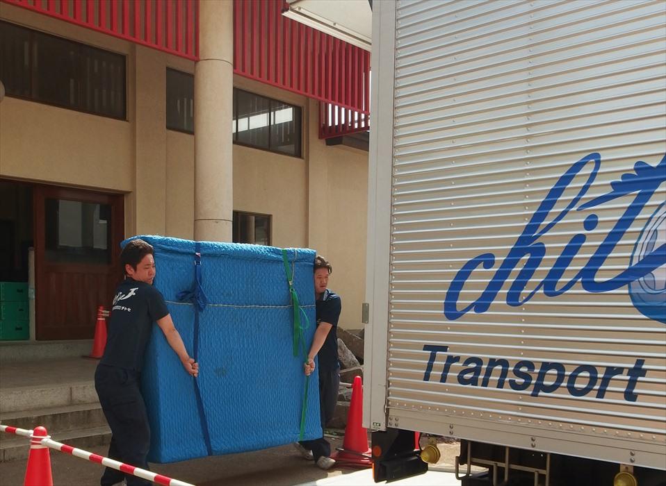 自社トラックに2名のスタッフが重量家具を運び入れる様子