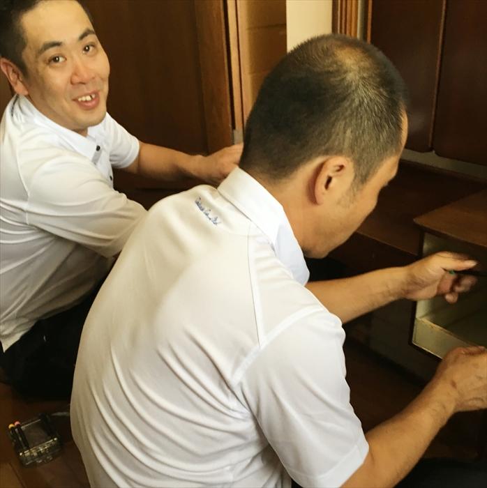 ドレッサーの引き出しを修理するスタッフ
