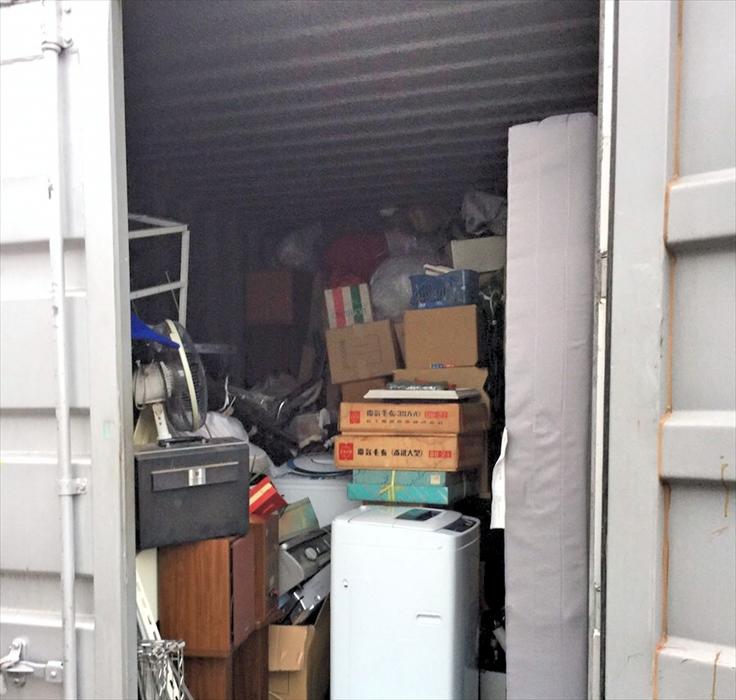 鉄製コンテナに乱雑に荷物が積まれた状態