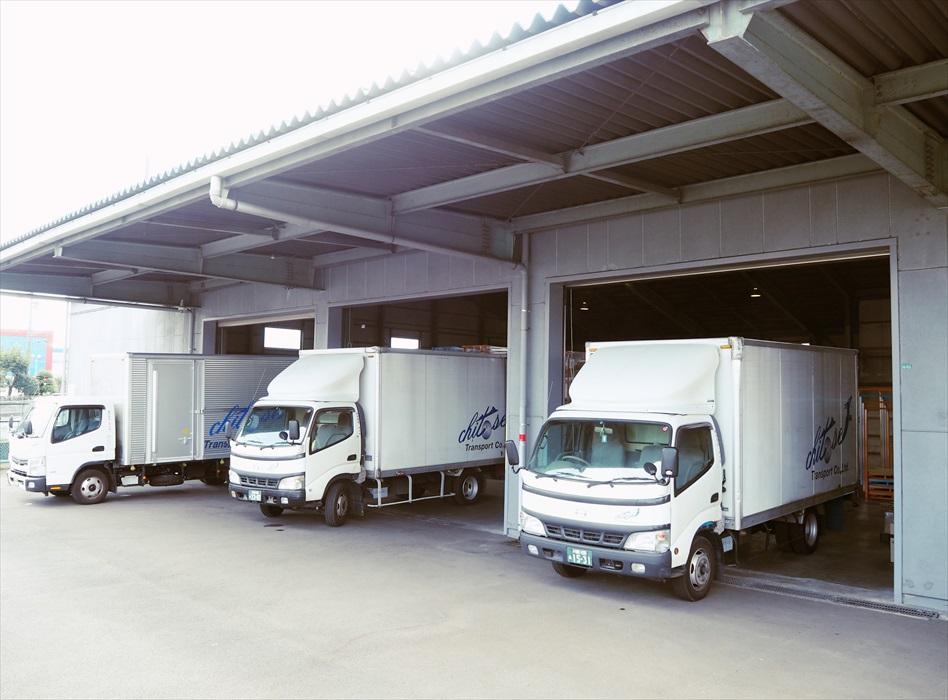 倉庫に3台のトラックが入庫する
