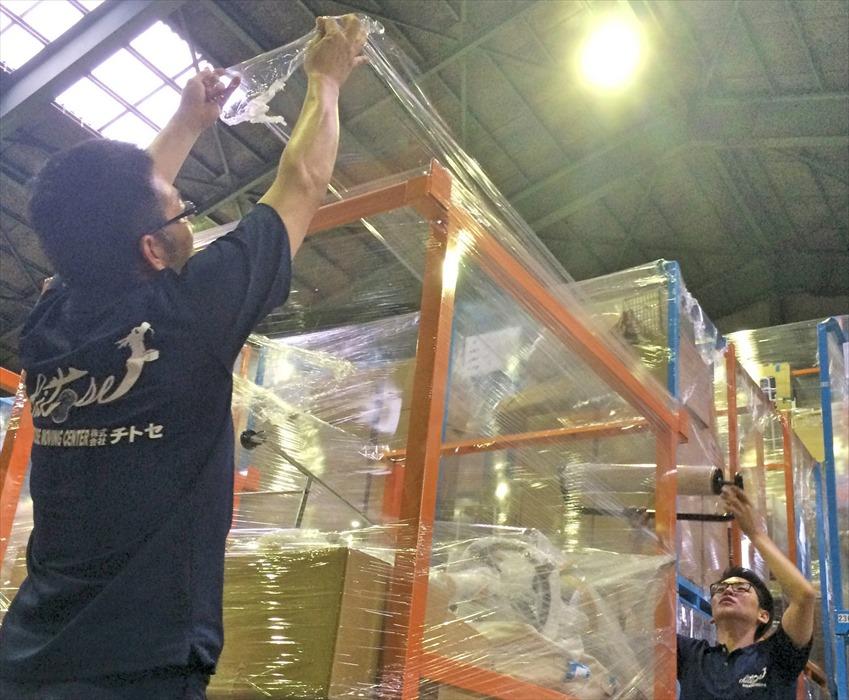 保管ラックに荷物を格納するスタッフ