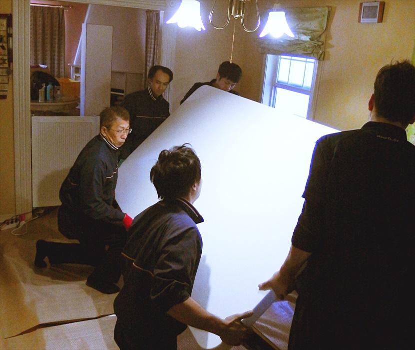 大理石テーブルを梱包するために逆に向けるスタッフ