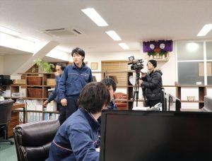 即日の引越と荷物預かりの準備をするスタッフを撮影するテレビカメラ