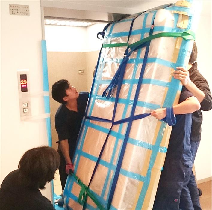 タワーマンションエレベーターへ大理石テーブルを運び入れるスタッフ