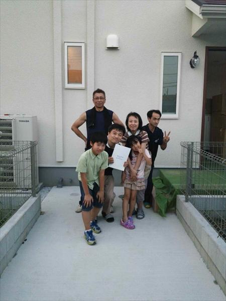 引越完了後にご新築の玄関前でご家族さまと撮影した記念写真