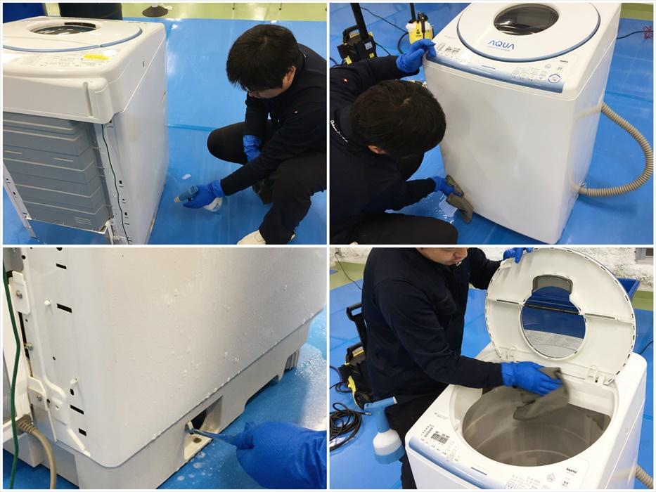 洗濯機の外装を洗浄するスタッフ