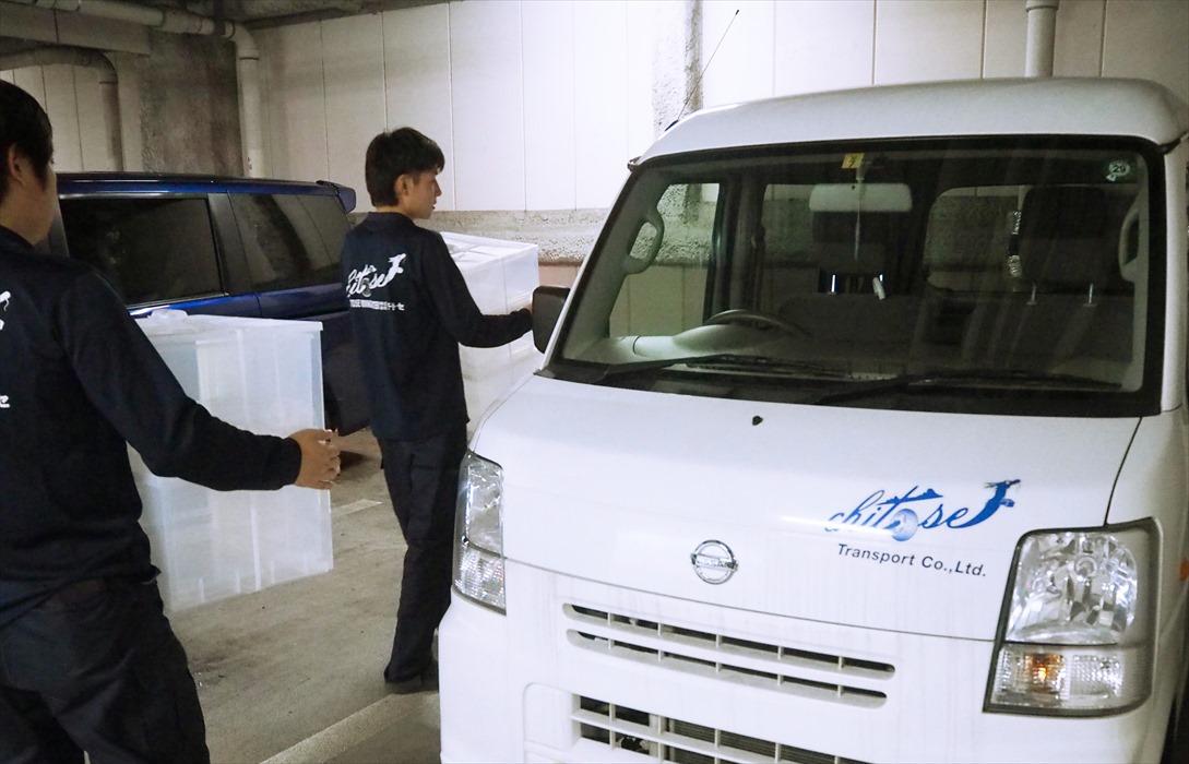 衣装ケースを軽ワゴンに運搬するスタッフ