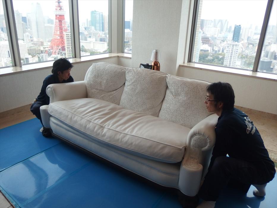 クロムハーツのレザー3人掛けソファを運ぼうとするスタッフ