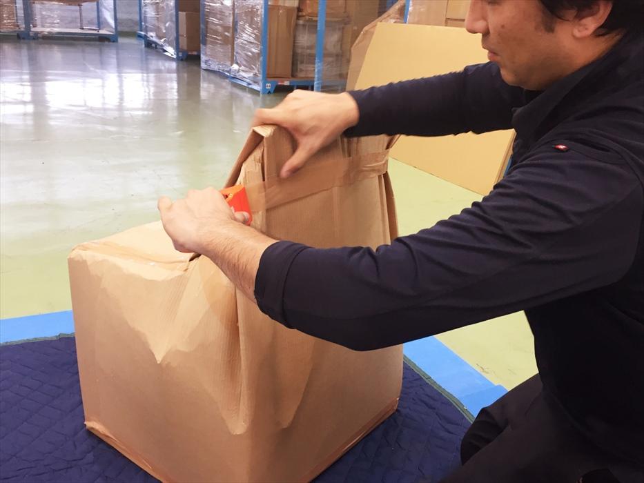 ダインニングチェアメタルの保管用梱包をするスタッフ.2