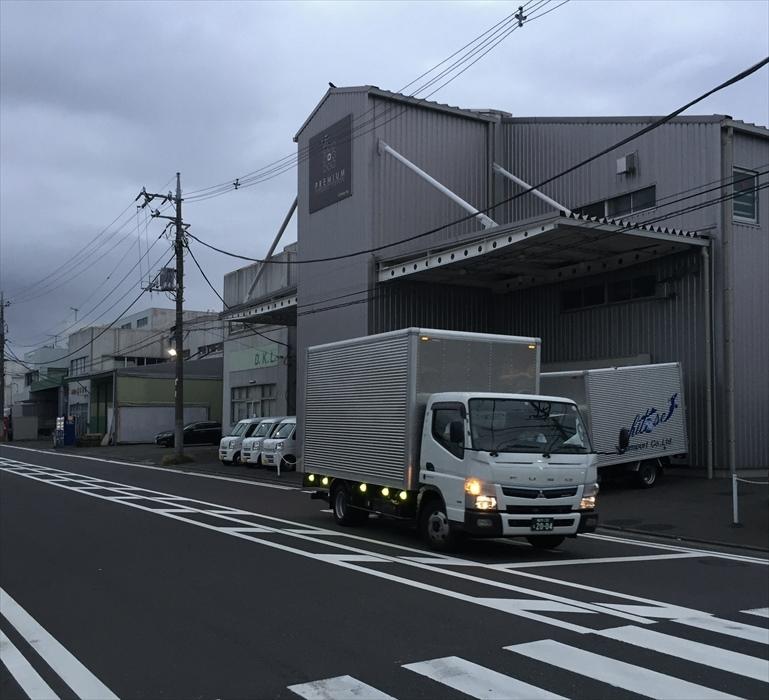 早朝保管倉庫を出発する自社トラック