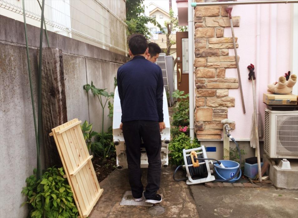 ドラム洗濯機を一戸建てに搬入するスタッフ