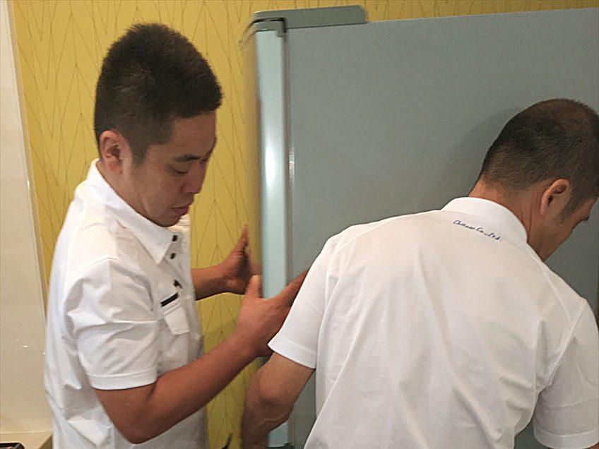 大型冷蔵庫を慎重に設置するスタッフ