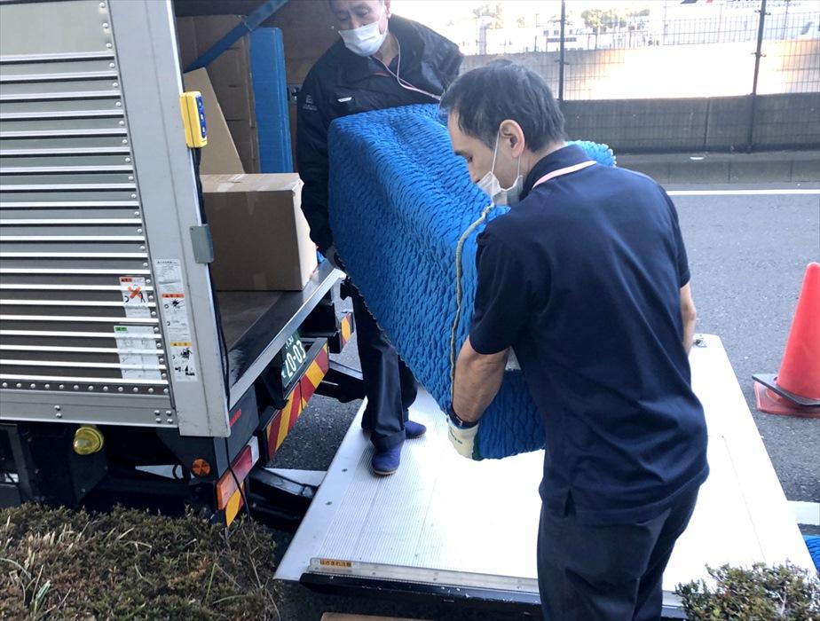 自社トラックにテレビボードを積載するスタッフ