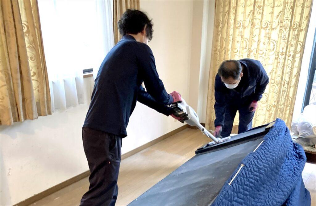 ソファを掃除するスタッフ